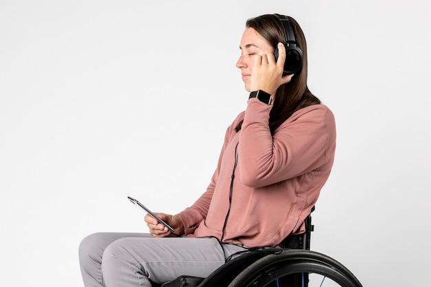 Fajna kobieta na wózku inwalidzkim słuchająca muzyki