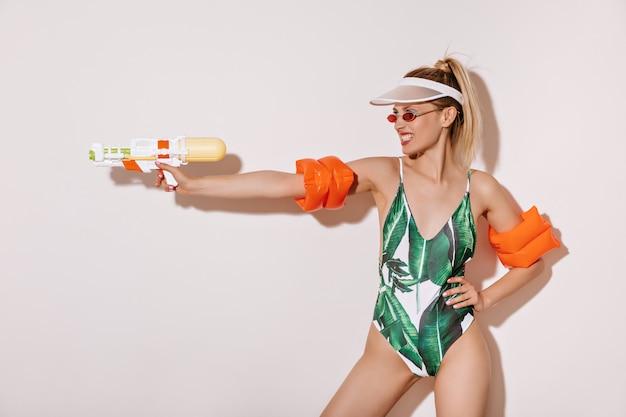 Fajna kobieta o blond włosach w czerwonych okularach przeciwsłonecznych, stylowej czapce i nowoczesnym stroju kąpielowym, trzymająca pistolet na wodę na białej izolowanej ścianie