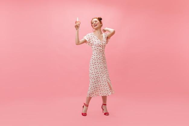 Fajna kobieta w białej sukni z wiśniami nadmuchuje konfetti na różowym tle.