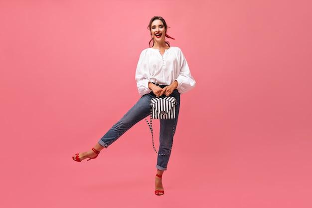 Fajna kobieta w dżinsach i bluzce, trzymając torbę na różowym tle. stylowa dziewczyna z czerwoną szminką i bandażem na włosach dobrze się bawi.