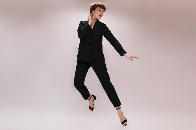 Fajna kobieta w garniturze skoki na białym tle. pełnometrażowy portret kobiety w czarnej kurtce i spodniach poruszających się na na białym tle