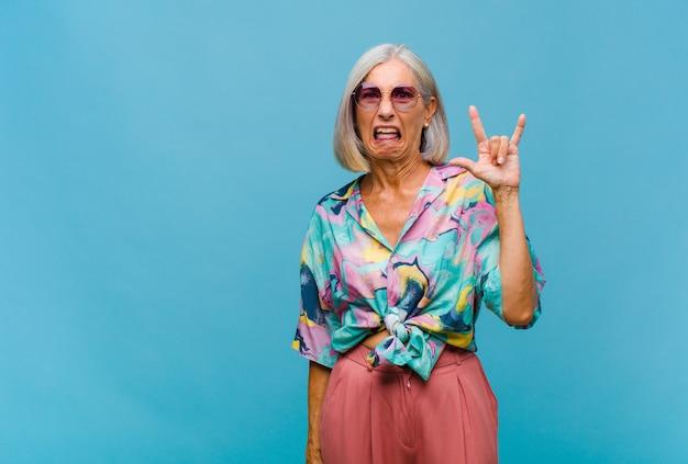 Fajna kobieta w średnim wieku czująca się szczęśliwa, zabawna, pewna siebie, pozytywna i zbuntowana, wykonująca ręką rockowy lub heavy metalowy znak