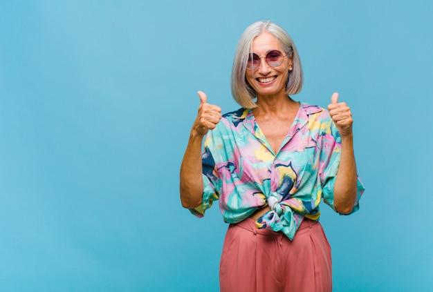 Fajna kobieta w średnim wieku, szeroko uśmiechnięta, szczęśliwa, pozytywna, pewna siebie i odnosząca sukcesy, z dwoma kciukami do góry