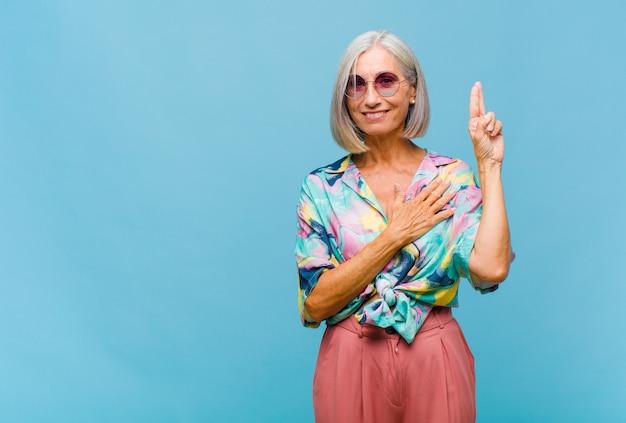 Fajna kobieta w średnim wieku, wyglądająca na szczęśliwą, pewną siebie i godną zaufania, uśmiechnięta i pokazująca znak zwycięstwa, z pozytywnym nastawieniem
