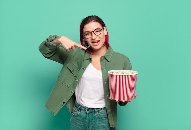 Fajna kobieta z czerwonymi włosami, popcornami i pilotem do telewizora