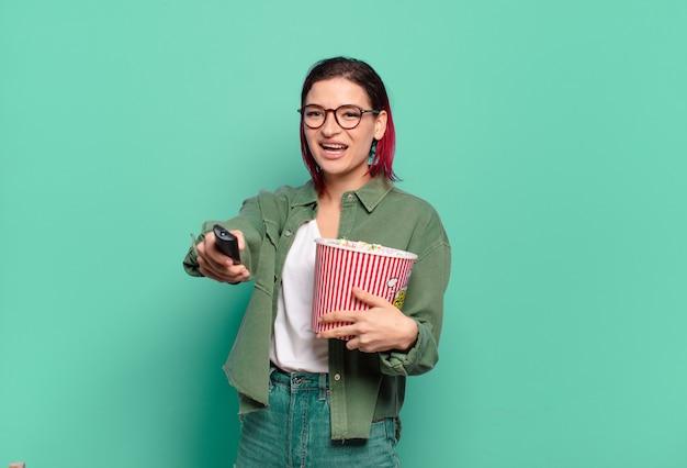 Fajna kobieta z rudymi włosami, popcornami i pilotem do telewizora