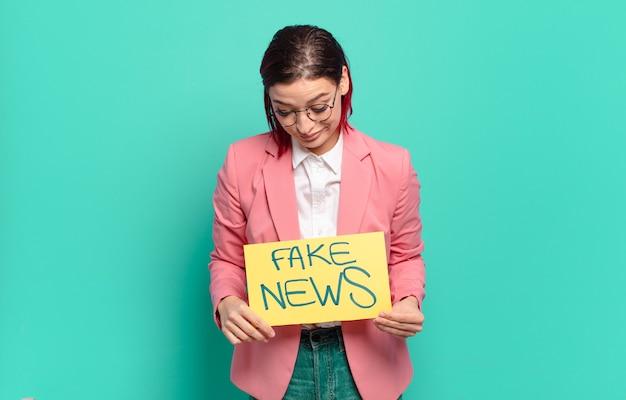 Fajna kobieta z rudymi włosami, trzymając tablicę z fałszywymi wiadomościami