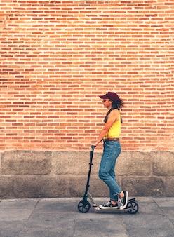 Fajna młoda kobieta jedzie ekologiczną hulajnogą w madrycie