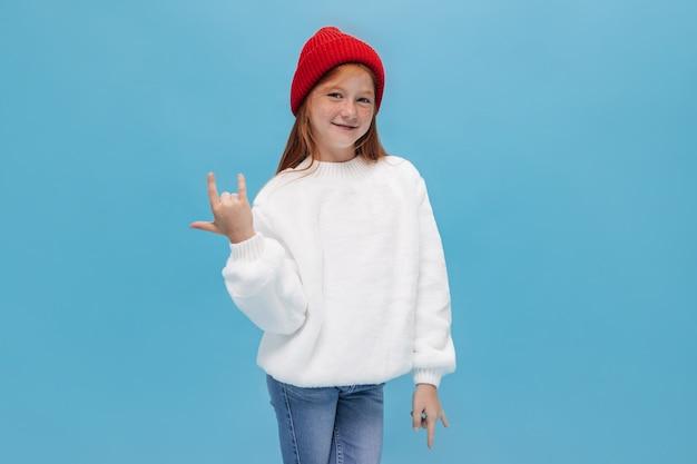 Fajna młoda rudowłosa dziewczyna z piegami i uroczym uśmiechem w białej szerokiej kanapie w dżinsach pokazuje znak rocka i patrzy na przód na niebieskiej ścianie