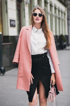 Fajna młoda stylowa piękna kobieta spacerująca po ulicy, ubrana w różowy płaszcz, torebkę, okulary przeciwsłoneczne, białą koszulę, czarną spódnicę, modny strój, jesienny trend, uśmiechnięty szczęśliwy, akcesoria