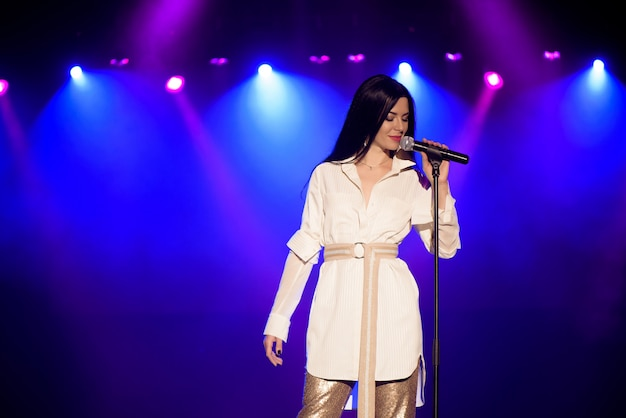 Fajna piosenkarka z mikrofonem na jasnej podświetlanej scenie w jasnych niebieskich światłach