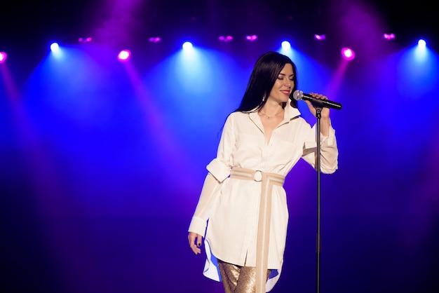 Fajna piosenkarka z mikrofonem na jasnej, podświetlanej scenie w jasnych niebieskich światłach.