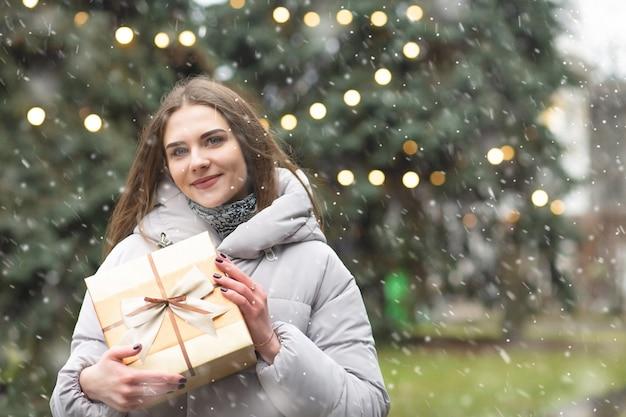 Fajne blond kobieta trzyma pudełko na ulicy podczas opadów śniegu. pusta przestrzeń