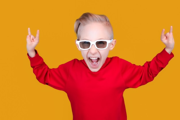 Fajne i wesołe dziecko w czerwonych ubraniach i okularach pokazuje gesty rąk na żółtym tle