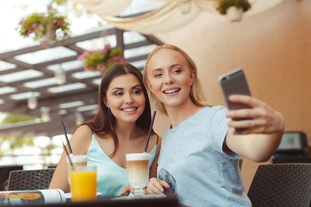 Fajne modne kobiety biorące selfie w kawiarni
