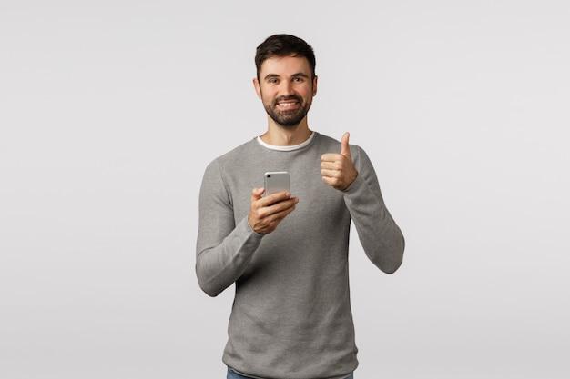Fajnie, dziękuję za rekomendację. wesoły przystojny brodaty mężczyzna w szarym swetrze trzyma smartfon, wykonaj gest kciukiem, jak aplikacja, reklamuj aplikację, zatwierdź urządzenie lub sklep internetowy