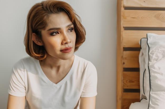 Fajnie wygląda kobieta w białej koszulce i dżinsach relaksuje się w swoim pokoju w mieszkaniu