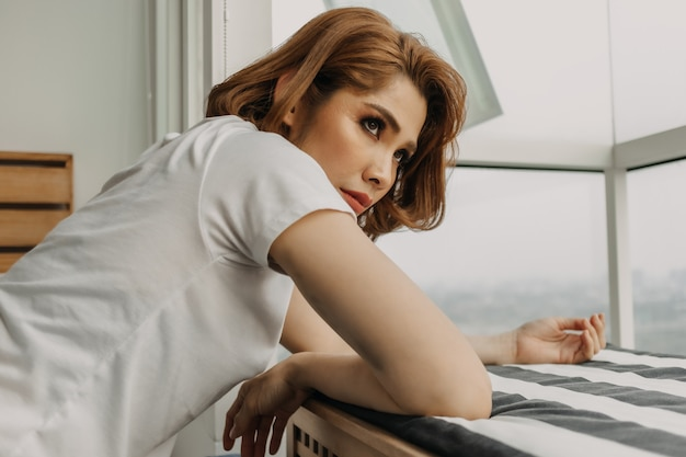Fajnie wyglądająca kobieta odpoczywa i ogląda widok ze swojego mieszkania