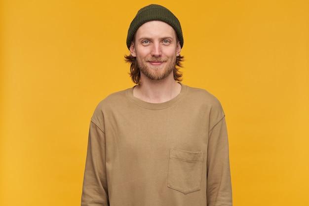 Fajnie wyglądający mężczyzna, przystojny brodaty facet o blond włosach. ubrana w zieloną czapkę i beżowy sweter. z pewnym siebie uśmiechem, odizolowany na żółtej ścianie