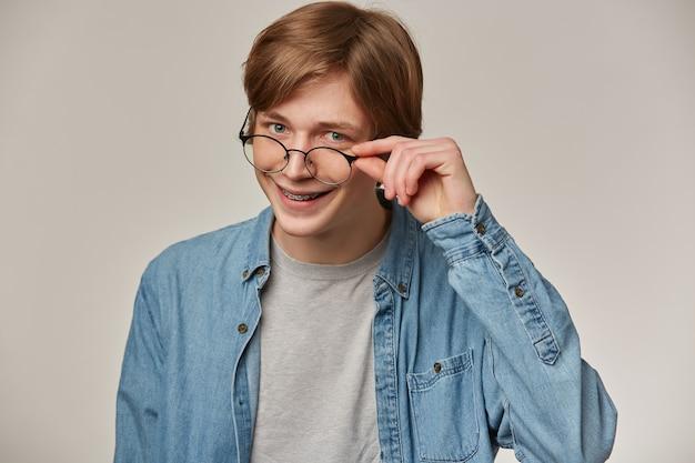 Fajnie wyglądający mężczyzna, przystojny facet o blond włosach. noszenie dżinsowej koszuli i okularów. posiada szelki. dotykając okularów i uśmiechając się. koncepcja emocji.