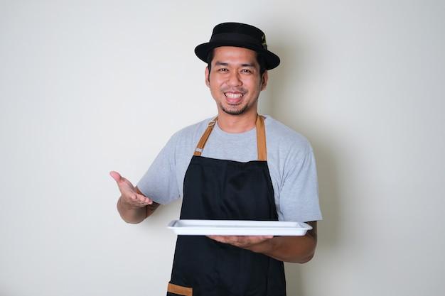 Fajny azjatycki barista ubrany w fartuch, trzymający pustą tacę i pokazujący szczęśliwy wyraz twarzy