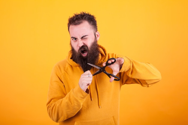 Fajny brodaty mężczyzna wyglądający na przerażonego podczas cięcia brody na żółtym tle. macho. styl życia