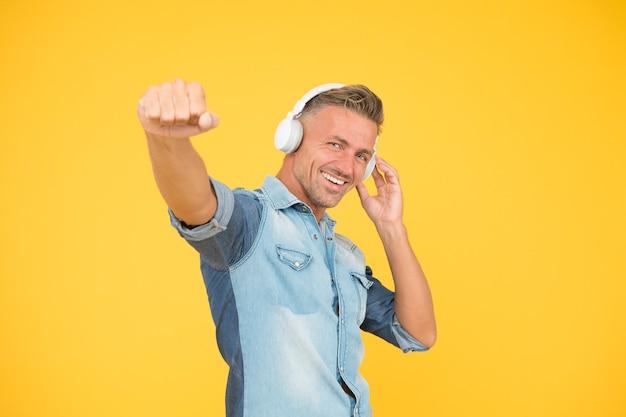 Fajny człowiek cieszyć się muzyką. jego ulubiona playlista. impreza dj. szczęśliwy człowiek tańczy na żółtym tle. słuchać muzyki w słuchawkach. złapać melodię. lubię ten utwór. melodia do tańca. seksowny facet w nastroju disco.