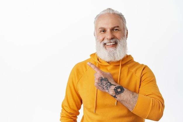 Fajny dziadek z długą brodą, ubrany w pomarańczową bluzę z kapturem, powyżej wyświetlający tekst promocyjny reklamy, biała ściana