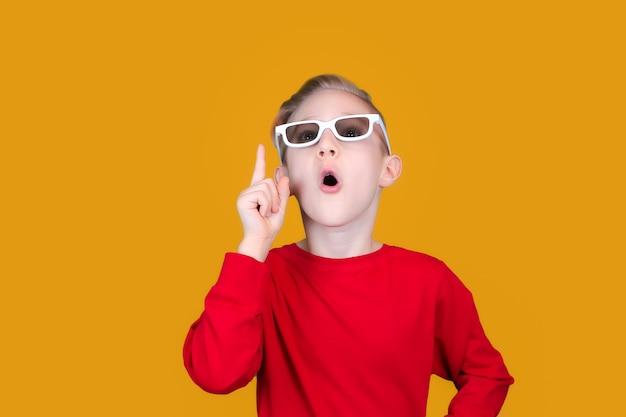 Fajny dzieciak w czerwonych ubraniach i okularach pokazujący emocje zaskoczenia na żółtym tle