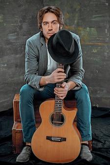 Fajny facet siedzi z gitarą na szarej przestrzeni