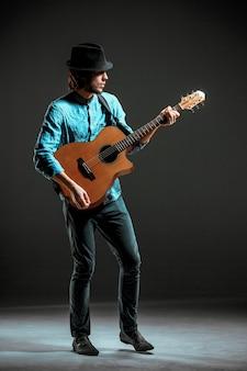 Fajny facet stojący z gitarą na ciemnej przestrzeni