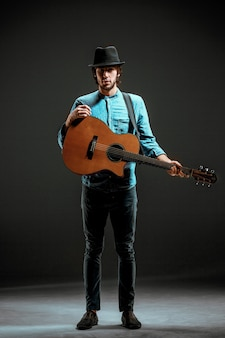 Fajny facet stojący z gitarą na ciemnej ścianie