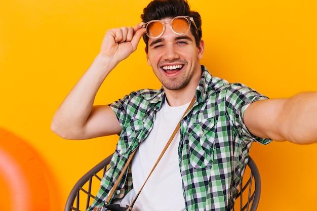 Fajny facet w białej koszulce i koszuli w kratę zdejmuje okulary, mruga i robi selfie w pomarańczowej przestrzeni.