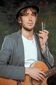 Fajny facet w kapeluszu, gra na gitarze i harmonijce ustnej na szarym tle studio