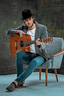 Fajny facet w kapeluszu, gra na gitarze na szarej przestrzeni