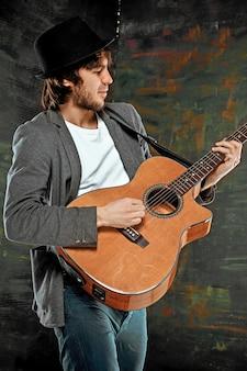 Fajny facet w kapeluszu, gra na gitarze na szarej ścianie