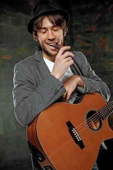 Fajny facet w kapeluszu grający na gitarze i harmonijce na szarym tle studyjnym