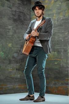 Fajny facet w kapeluszu grający na gitarze na szarym tle studyjnym