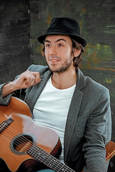 Fajny facet w kapeluszu siedzi z gitarą na szarym tle studio