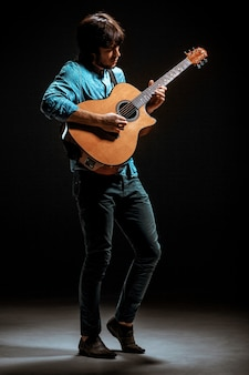Fajny facet w kapeluszu stojący z gitarą na ciemnym tle studia