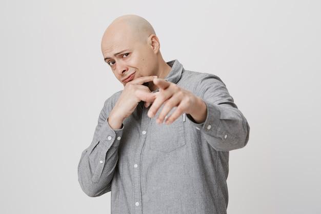 Fajny łysy facet wskazujący palcem z przodu