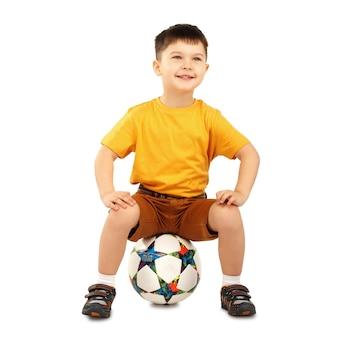 Fajny mały chłopiec siedzi na piłki nożnej na białym tle