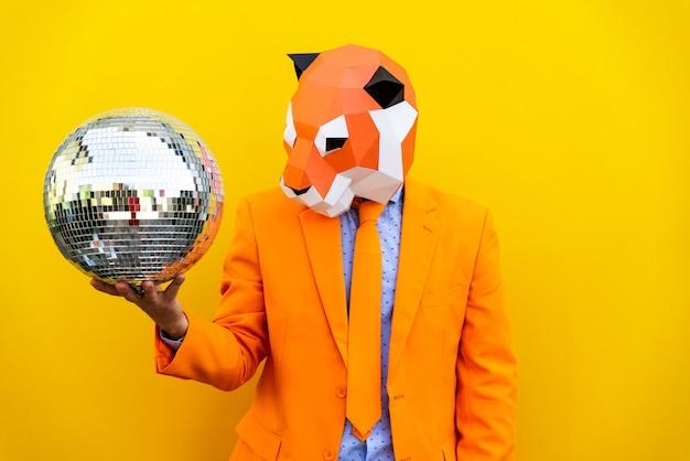 Fajny mężczyzna w masce 3d origami ze stylowymi kolorowymi ubraniami kreatywna koncepcja reklamy maski na głowę zwierzęcia robi zabawne rzeczy na kolorowym tle