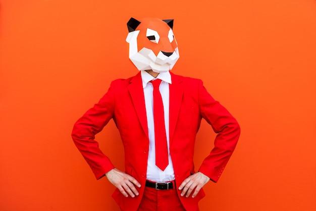Fajny mężczyzna w masce 3d origami ze stylowymi kolorowymi ubraniami - kreatywna koncepcja reklamy, zwierzęca maska na głowie robi śmieszne rzeczy na kolorowym tle