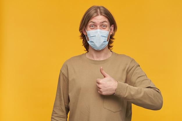 Fajny mężczyzna, wesoły brodaty facet z blond fryzurą. noszenie beżowego swetra i medycznej maski ochronnej. pokazuje znak zatwierdzenia, kciuk w górę. pojedynczo na żółtej ścianie