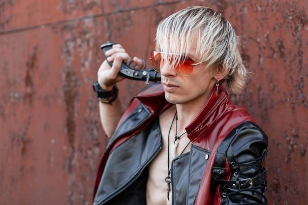 Fajny młody blondyn z nagim torsem w modnej czerwono-czarnej skórzanej kurtce, w czerwonych okularach, pozuje w pobliżu starego zardzewiałego budynku. przystojny facet z rocznika pistoletem. przyszły styl punkowy