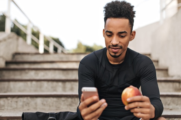 Fajny młody brunetka mężczyzna w czarnej koszulce z długimi rękawami patrzy na ekran telefonu, siedzi na schodach na zewnątrz i trzyma świeże jabłko