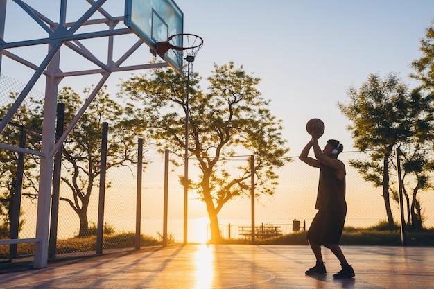 Fajny młody człowiek uprawiający sport, grający w koszykówkę o wschodzie słońca