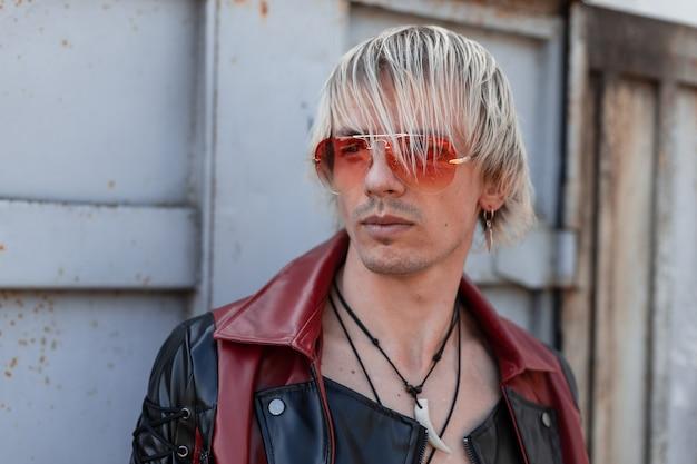 Fajny młody człowiek w czarno-czerwonej skórzanej kurtce vintage w modnych okularach przeciwsłonecznych z fryzurą na zewnątrz, w pobliżu metalicznej szarej ściany.
