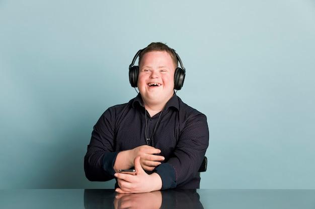 Fajny młody człowiek z zespołem downa słucha podcastu sportowego